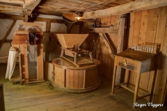 The water mill grinding floor. The hopper feeds grain inot the grindstones (in the circular case) which then falls through a chute into a sack.